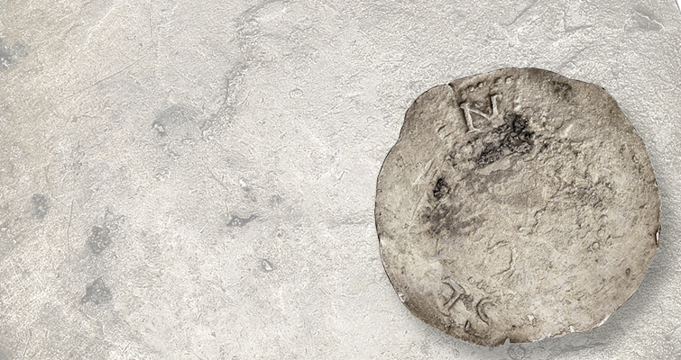 Damaged by saltwater, this 1652 Willow Tree shilling is from a 1711 shipwreck