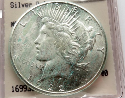 This 1922-S Peace Dollar has telltale PVC problems (green streaks) from being stored in a soft vinyl flip. But it can be saved.