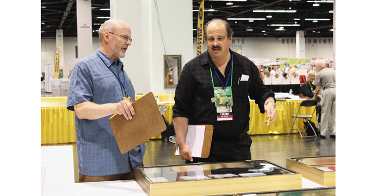 Exhibit judges Kerry Wetterstrom, left, and Steve D'Ippolito review winning collector exhibits in various categories to determine the Best-in-Show winner during the American Numismatic Association World's Fair of Money Aug. 11 in Anaheim.