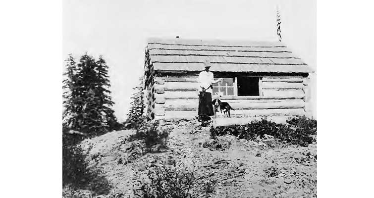Hallie Daggett and her dog outside the Eddy's Gulch Lookout Station on top of Klamath Peak.