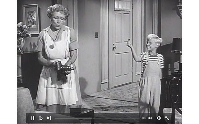 Dennis the Menace shows Mrs. Wilson the coin he found on the floor in this screen grab from