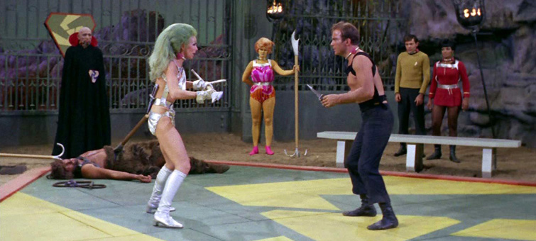 "In a scene from the episode ""Gamesters of Triskelion"" from the original Star Trek television program, Capt. James T. Kirk prepares to fight with a ""drill thrall"" called Shahna while (unseen here) the Providers wager on the outcome in the currency unit called the ""quatloo."""