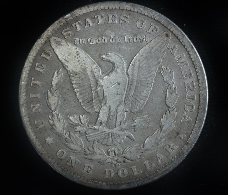 "Hobbyists call the result of a die gouge on the 1890-CC dollar coin a ""tailbar"" because a bar seems to extend from the right tail feathers of the eagle."